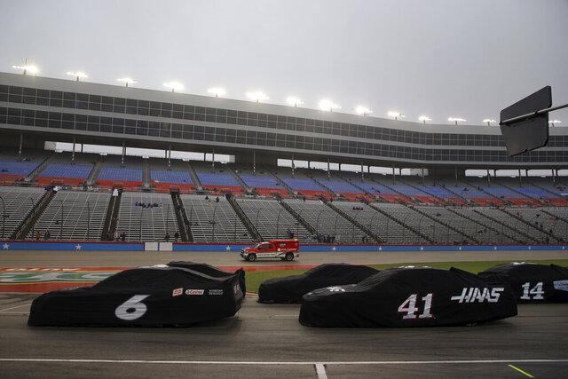 Cars sit on pit road during a red flag period due to misty rain during a NASCAR Cup Series auto race at Texas Motor Speedway in Fort Worth, Texas, Sunday, Oct. 25, 2020. (AP Photo/Richard W. Rodriguez)