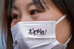 """A woman wearing a face mask with the words """"Gaokao, must win"""" as students take part on the first day of China's national college entrance examinations, known as the gaokao, in Beijing, Monday, June 7, 2021WLD. More than 10 million high school students throughout China will take the two days annual college entrance exams which start on Monday to Tuesday, according to the state media report. (AP Photo/Andy Wong)"""