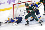St. Louis Blues goalie Jake Allen, left, sprawls on the ice while making a save as Vince Dunn, right, keeps close defense on Minnesota Wild's Joel Eriksson Ek, of Sweden, during the first period of an NHL hockey game Saturday, Nov. 2, 2019, in St. Paul, Minn. (AP Photo/Jim Mone)