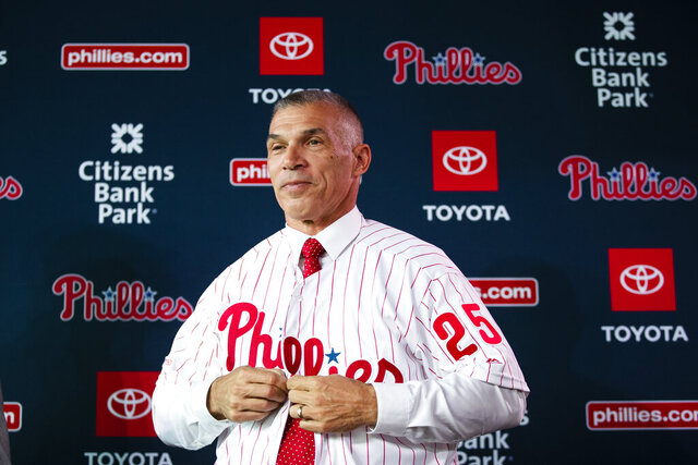 FILE - In this Oct. 28, 2019, file photo, the Philadelphia Phillies' new manager, Joe Girardi puts on his uniform during a news conference in Philadelphia. The Phillies enter spring training with a new manager who has a winning pedigree. Girardi, who led the Yankees to a World Series title, takes over in Philadelphia while righty Zack Wheeler and shortstop Didi Gregorious were the biggest on-field additions.  (AP Photo/Matt Rourke, File)