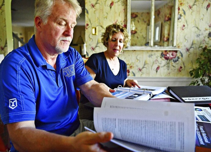In this June 20, 2019, photo, Dr. Greg Foy, left, and his wife Leigh Foy discuss their upcoming climate change workshop during an interview at their home in Spring Garden Township, Pa. (Dawn J. Sagert/York Dispatch via AP)
