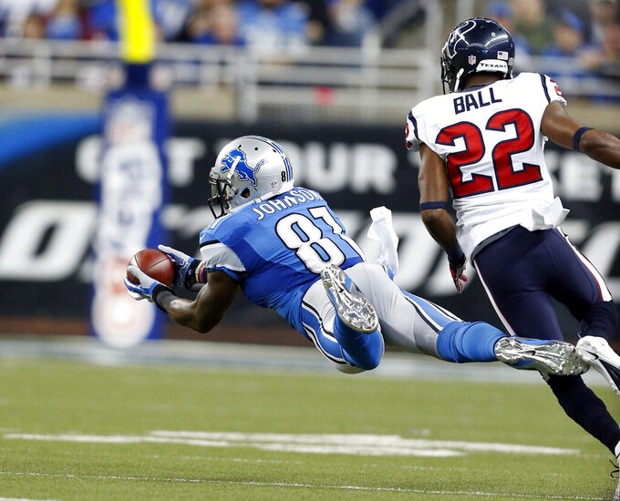 FILE - In this Nov. 22, 2012, file photo, Detroit Lions wide receiver Calvin Johnson (81) makes a diving catch as Houston Texans defensive back Alan Ball (22) defends during the first quarter of an NFL football game in Detroit. With the NFL increasing its season to 17 games for the first change in length of the season since going from 14 to 16 games in 1978, some records and milestones could soon be threatened by even more players. In an era where records have been falling with frequency, one mark that hasn't been reached is 2,000 yards receiving in a season. Johnson came closest with 1,964 yards in 2012. (AP Photo/Rick Osentoski, File)