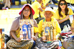 Well-wishers hold the portraits of Thailand's King Maha Vajiralongkorn and Queen Suthida outside the Grand Palace in Bangkok, Thailand, Thursday, Dec. 12, 2019. Thailand's King  attended the Royal Barge Procession, considered the final phase in his coronation as King Rama X. The ceremonial water-borne procession reserved for the river journeys of kings in royal ceremonies will be the first in the present reign. (AP Photo/Suganya Samnangjam)