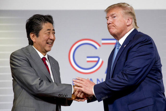 FILE - In this Aug. 25, 2019, file photo, U.S President Donald Trump and Japanese Prime Minister Shinzo Abe shake hands following a news conference at the G-7 summit in Biarritz, France to announce that the U.S. and Japan have agreed in principle on a new trade agreement. On Tuesday, Sept. 17, 2019, officials in Japan appear wary over the prospects for a trade deal with the U.S. after President Donald Trump said he was prepared to sign a pact soon. (AP Photo/Andrew Harnik, File)