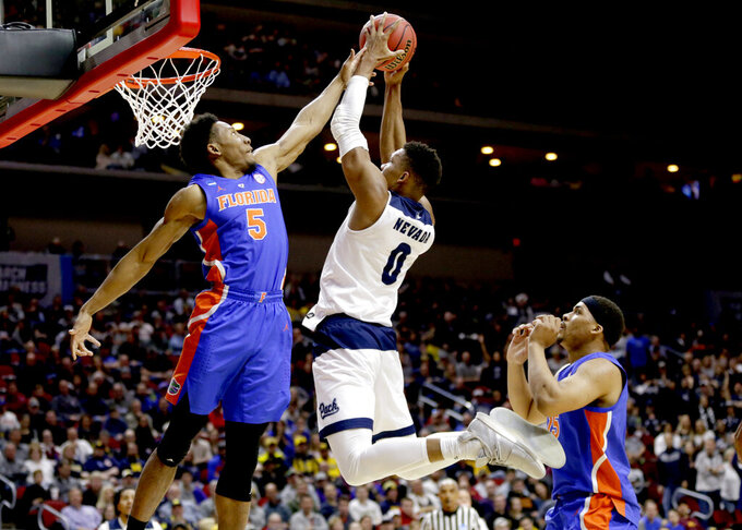 Nevada's Tre'Shawn Thurman (0) goes to the basket against Florida's KeVaughn Allen (5) and Isaiah Stokes, right, during the first half of a first round men's college basketball game in the NCAA Tournament, in Des Moines, Iowa, Thursday, March 21, 2019. (AP Photo/Nati Harnik)