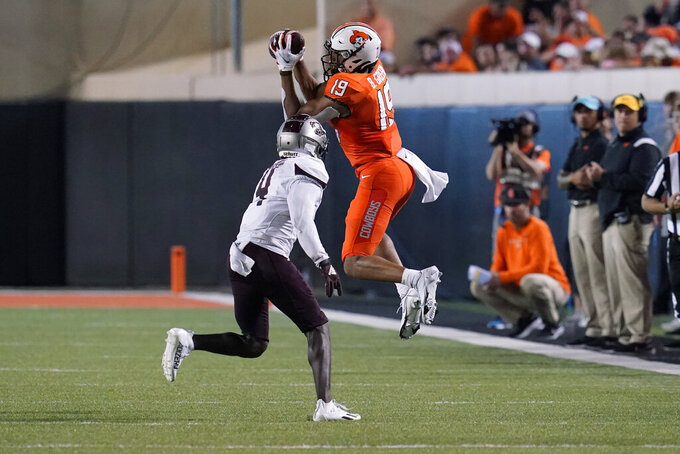 Oklahoma State wide receiver Bryson Green (19) catches a pass in front of Missouri State cornerback Montrae Braswell (4) during the second half of an NCAA college football game Saturday, Sept. 4, 2021, in Stillwater, Okla. (AP Photo/Sue Ogrocki)