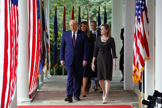 President Donald Trump walks along the Colonnade with Judge Amy Coney Barrett to a news conference to announce Barrett as his nominee to the Supreme Court, in the Rose Garden at the White House, Saturday, Sept. 26, 2020, in Washington. (AP Photo/Alex Brandon)