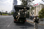 Chilean Army soldiers jump from a truck during a protest in Santiago, Chile, Saturday, Oct. 19, 2019. The protests started on Friday afternoon when high school students flooded subway stations, jumping turnstiles, dodging fares and vandalizing stations as part of protests against a fare hike, but by nightfall had extended throughout Santiago with students setting up barricades and fires at the entrances to subway stations, forcing President Sebastian Pinera to announce a state of emergency and deploy the armed forces into the streets. (AP Photo/Esteban Felix)
