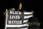 A woman holds a flag while yelling during a protest over the fatal shooting of Daunte Wright by a police officer during a traffic stop, Saturday, April 17, 2021, outside the Brooklyn Center Police Department in Brooklyn Center, Minn. (AP Photo/Julio Cortez)