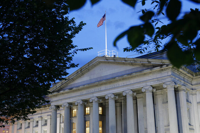 File-This Thursday, June 6, 2019, photo shows the U.S. Treasury Department building at dusk, in Washington. The Treasury Department is projecting government borrowing of $947 billion in the current July-September period, which would be a record for the quarter but down from the all-time high of $2.75 trillion in this year's second quarter. Treasury officials announced Monday, Aug. 3, 2020, that the government also plans to borrow $1.22 trillion in the October-December period. (AP Photo/Patrick Semansky, File)