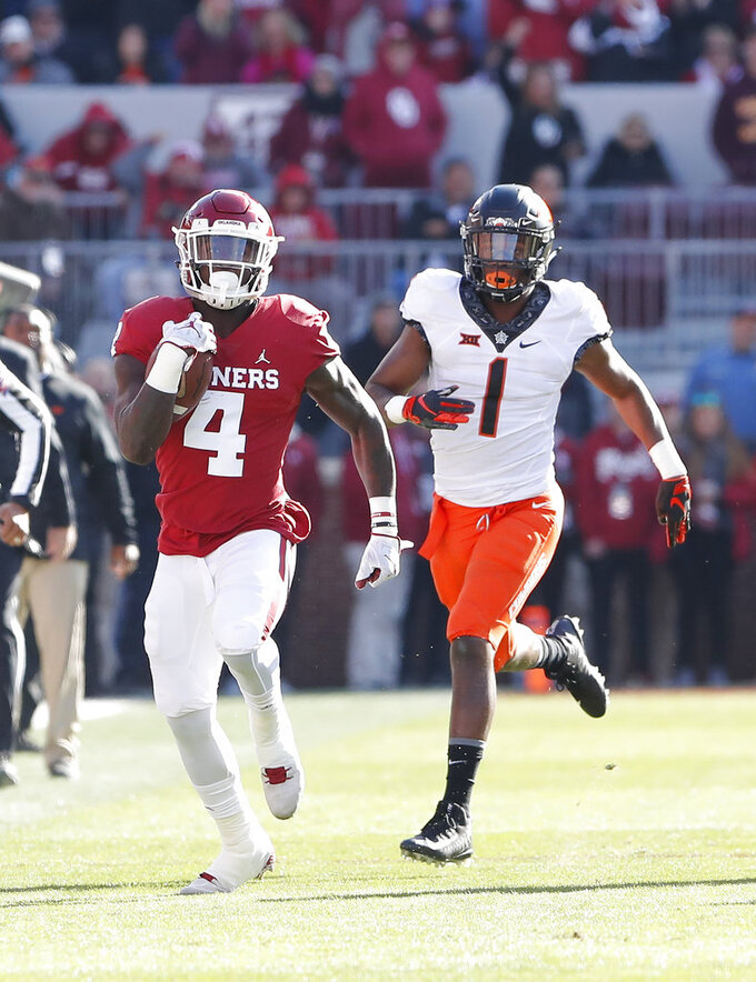 Oklahoma running back Trey Sermon (4) runs ahead of Oklahoma State linebacker Calvin Bundage (1) in the first quarter of an NCAA college football game in Norman, Okla., Saturday, Nov. 10, 2018. (AP Photo/Alonzo Adams)