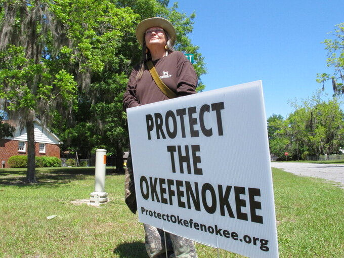 """Jane Winkler stands with a sign that says """"Protect The Okefenokee"""" outside a church where Georgia Gov. Brian Kemp met with local Chamber of Commerce members in Folkston, Ga., on April 22, 2021. Winkler and others are fighting a mining company's plan to dig for minerals about 3 miles from the edge of the Okefenokee National Wildlife Refuge. The company Twin Pines Minerals says it can mine the area without harming the swamp. But federal government scientists have said the project could damage the swamp's ability to hold water. (AP Photo/Russ Bynum)"""