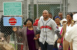 FILE - In this April 17, 2003 photo, Terry Harrington, center, leaves the Clarinda Correctional Facility with his mother Josephine James, left, and daughter Nicole Brown, right, after Iowa Gov. Tom Vilsack signed a reprieve for Harrington, in Clarinda, Iowa. Harrington, who spent more than 25 years in prison for an Iowa murder that he did not commit is urging college students to help inmates who may be innocent. Terry Harrington spoke to Coe College students on Tuesday, Oct. 8, 2019, recounting how he was wrongly convicted in the 1977 shooting death of a Council Bluffs security guard when he was a teenager. (AP Photo/Charlie Neibergall File)