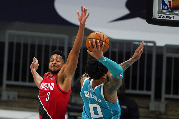 Charlotte Hornets forward Miles Bridges dunks past Portland Trail Blazers guard CJ McCollum during the first half in an NBA basketball game on Sunday, April 18, 2021, in Charlotte, N.C. (AP Photo/Chris Carlson)