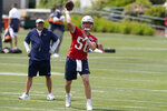 New England Patriots quarterback Mac Jones (50) passes the ball as offensive coordinator Josh McDaniels, left, looks on during an NFL football practice in Foxborough, Mass., Thursday, June 10, 2021. (AP Photo/Steven Senne)