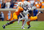 Mississippi State wide receiver Osirus Mitchell (5) runs for yardage as he's hit by Tennessee defensive back Bryce Thompson (20) and defensive back Nigel Warrior (18) in the first half of an NCAA college football game Saturday, Oct. 12, 2019, in Knoxville, Tenn. (AP Photo/Wade Payne)