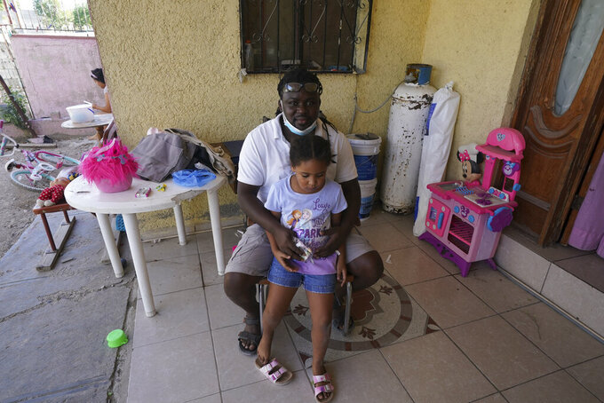 Mensah Montant and his daughter Rachel sit on their porch in Ciudad Acuna, Friday, Sept. 24, 2021. Montant, from the African nation of Togo, and his wife, are among the Acuna residents who are responding to the needs of Haitian migrants. (AP Photo/Fernando Llano)