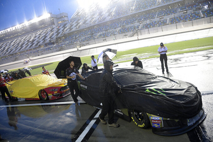 Crew members of Kurt Busch, right, and Joey Logano (22) push their cars off pit road after a NASCAR Cup Series auto race was postponed to the next day at Daytona International Speedway, Saturday, July 6, 2019, in Daytona Beach, Fla. (AP Photo/Phelan M. Ebenhack)