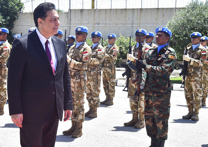 In this photo released by Lebanon's official government photographer Dalati Nohra, Lebanese Prime Minister Hassan Diab reviews the honor guard of the United Nations peacekeepers, upon his arrival at their headquarters in the southern coastal border town of Naqoura, Lebanon, Wednesday, May 27, 2020. The visit comes against the backdrop of a war of words between Israel and Lebanese officials, including the powerful Hezbollah group, over the mandate of the U.N. troops, known as UNIFIL, deployed in southern Lebanon since an Israel invasion in 1978. (Dalati Nohra via AP)