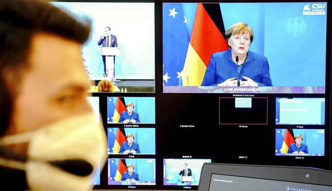 German Chancellor Angela Merkel is seen on a screen, making a statement on the events in Washington with the storming of the Capitol by Trump supporters at the beginning of the digital press conference at the winter retreat of the CSU parliamentary group in the Bundestag, Berlin, Germany, Thursday, Jan. 7, 2021. (Kay Nietfeld/Pool via AP)