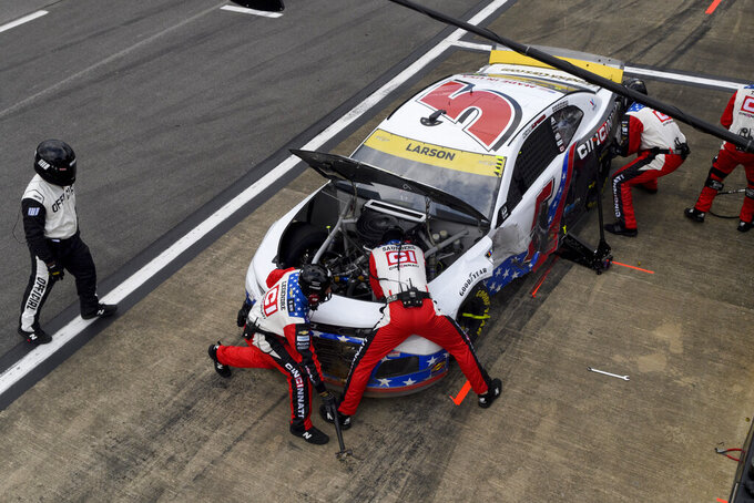 Crew tend to a car driven by Kyle Larson during a pit stop in a NASCAR Cup series auto race Monday, Oct. 4, 2021, in Talladega, Ala. (AP Photo/John Amis)