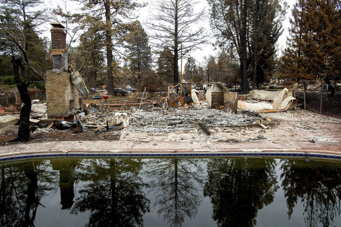 FILE - In this Dec. 3, 2018, file photo, trees reflect in a swimming pool outside Erica Hail's Paradise, Calif., home, which burned during the Camp Fire. Water officials say the drinking water in Paradise, which was decimated by a wildfire last year, is contaminated with the cancer-causing chemical benzene. Fixing the problem could cost $300 million and take up to two years. The Sacramento Bee reports Thursday, April 18, 2019, experts believe the extreme heat of the November firestorm created a