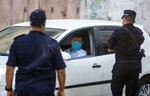 Palestinian Hamas policemen stop vehicles during a 48 hour lockdown imposed following the discovery of the first coronavirus cases in the Gaza Strip, Tuesday, Aug. 25, 2020. (AP Photo/Khalil Hamra)