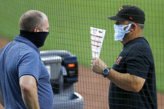 Baltimore Orioles director of baseball administration Kevin Buck, left, and field coordinator Tim Cossins wear masks to protect against COVID-19 as they talk during an intrasquad game at baseball training camp Tuesday, July 14, 2020, in Baltimore. (AP Photo/Julio Cortez)