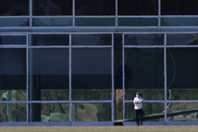 Brazil's President Jair Bolsonaro stands with his arms crossed outside the official presidential residence, Alvorada Palace, in Brasilia, Brazil, Wednesday, July 8, 2020. Bolsonaro said Tuesday he tested positive for COVID-19. (AP Photo/Eraldo Peres)
