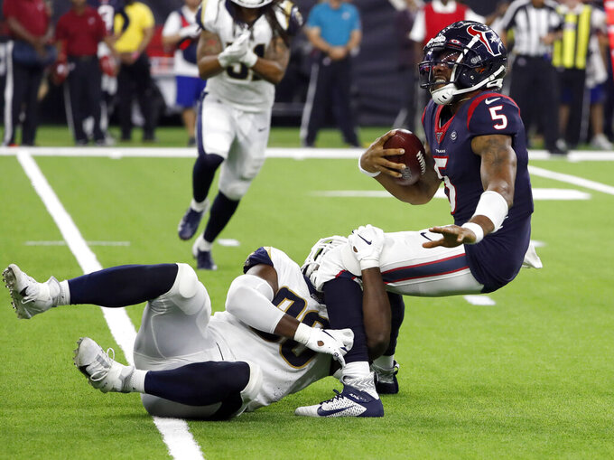 Houston Texans quarterback Joe Webb III (5) is tackled by Los Angeles Rams linebacker Landis Durham (96) during the second half of a preseason NFL football game Thursday, Aug. 29, 2019, in Houston. (AP Photo/Kevin M. Cox)