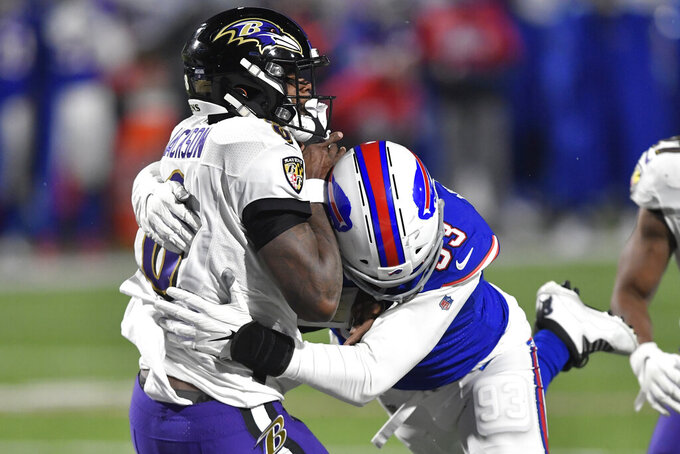 Baltimore Ravens quarterback Lamar Jackson (8) is hit by Buffalo Bills' Trent Murphy (93) during the second half of an NFL divisional round football game Saturday, Jan. 16, 2021, in Orchard Park, N.Y. Jackson was injured on the play. (AP Photo/Adrian Kraus)