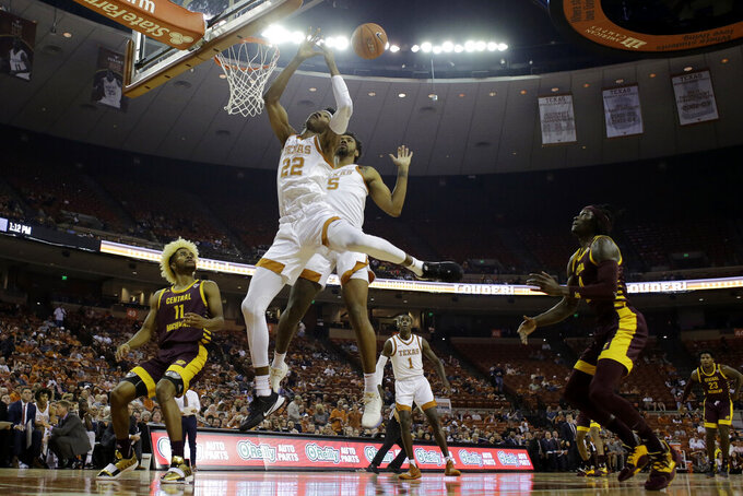 Texas forward Kai Jones (22) and forward Royce Hamm Jr. (5) reach for a rebound during the first half of an NCAA college basketball game against Central Michigan , Saturday, Dec. 14, 2019, in Austin, Texas. (AP Photo/Eric Gay)