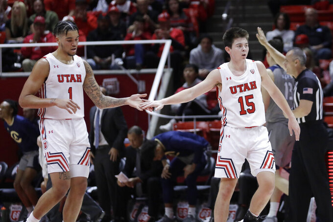 Utah's Timmy Allen (1) and Rylan Jones (15) celebrate a score during the first half against UC Davis in an NCAA college basketball game Friday, Nov. 29, 2019, in Salt Lake City. (AP Photo/Rick Bowmer)