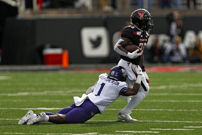 TCU's Tre'Vius Hodges-Tomlinson (1) tackles Texas Tech's Ta'Zhawn Henry (26) during the first half of an NCAA college football game against TCU, Saturday, Nov. 16, 2019, in Lubbock, Texas. (Brad Tollefson/Lubbock Avalanche-Journal via AP)