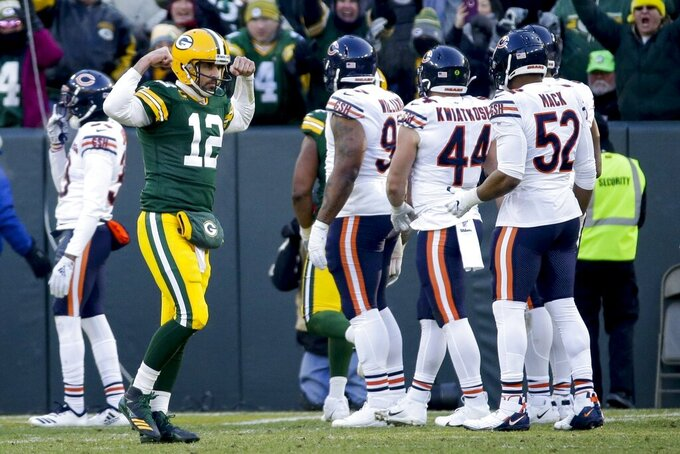 FILE - Green Bay Packers' Aaron Rodgers celebrates after Aaron Jones ran for a touchdown during the second half of an NFL football game against the Chicago Bears, Sunday, Dec. 15, 2019, in Green Bay, Wis. Aaron Rodgers will begin his 16th season with Green Bay looking  to continue his remarkable run of success against NFC North opponents as the Packers visit Minnesota. The Packers own a 47-18-1 record in games Rodgers has played against NFC North foes, including a 6-0 mark last season. (AP Photo/Mike Roemer, File)