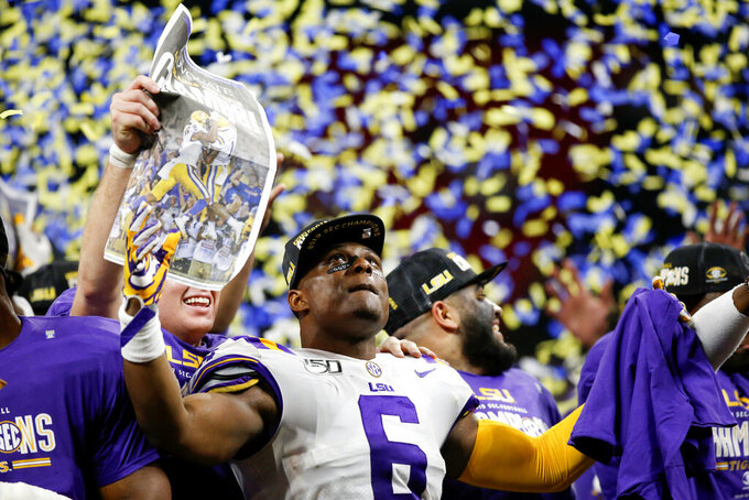 LSU linebacker Jacob Phillips (6) celebrates on stage after LSU defeated Georgia during an NCAA college football game for the Southeastern Conference championship on Saturday, Dec. 7, 2019, in Atlanta. (C.B. Schmelter/Chattanooga Times Free Press via AP)