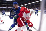 Vancouver Canucks' Jake Virtanen checks Detroit Red Wings' Darren Helm (43) during the first period of an NHL hockey game Tuesday, Oct. 15, 2019, in Vancouver, British Columbia. (Ben Nelms/The Canadian Press via AP)