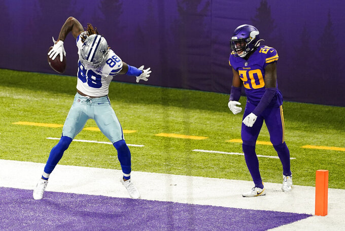 Dallas Cowboys wide receiver CeeDee Lamb (88) celebrates in front of Minnesota Vikings cornerback Jeff Gladney, right, after catching a 4-yard touchdown pass during the first half of an NFL football game, Sunday, Nov. 22, 2020, in Minneapolis. (AP Photo/Jim Mone)