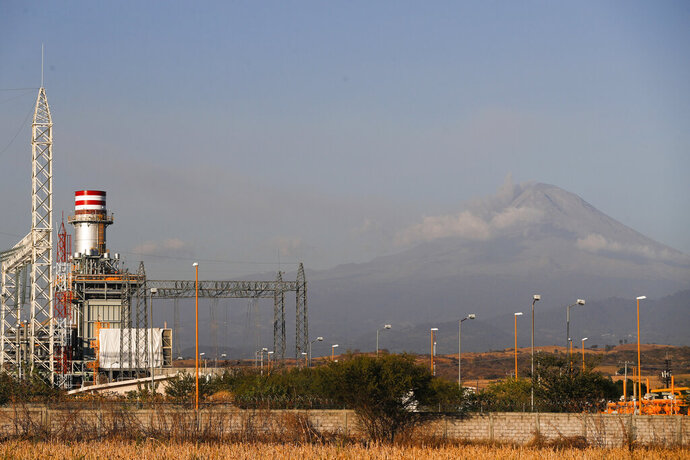 A newly built power generation plant stand idle with the Popocatepetl Volcano in the background, near Huexca, Morelos state, Mexico, Saturday, Feb. 22, 2020. Dozens of mostly indigenous communities along the 159 kilometers of pipeline have united to fight the mega-project they believe will deprive them of water for their crops, while contaminating the soil and air. (AP Photo/Eduardo Verdugo)