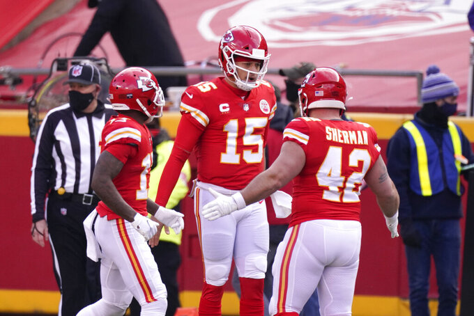 Kansas City Chiefs quarterback Patrick Mahomes (15) celebrates with teammates after scoring on a touchdown run during the first half of an NFL divisional round football game against the Cleveland Browns, Sunday, Jan. 17, 2021, in Kansas City. (AP Photo/Charlie Riedel)