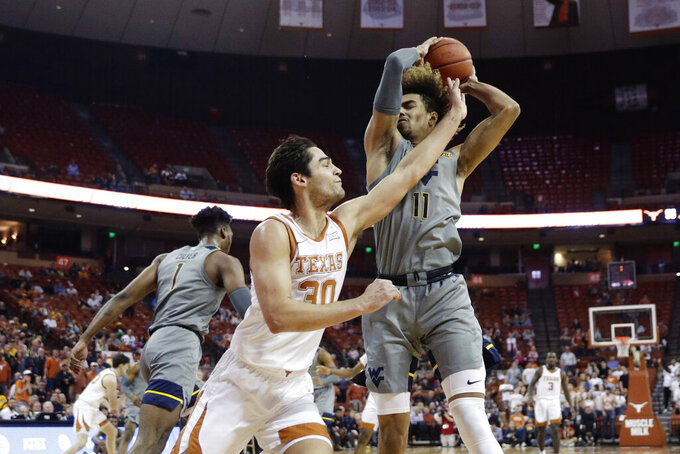 West Virginia forward Emmitt Matthews Jr. (11) pulls down a rebound over Texas forward Brock Cunningham (30) during the second half of an NCAA college basketball game, Monday, Feb. 24, 2020, in Austin, Texas. (AP Photo/Eric Gay)