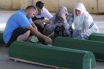 Bosnians sit by the coffins of their relatives inside the former UN base in Potocari, near Srebrenica, Bosnia, Friday, July 10, 2020. Nine newly found and identified men and boys will be laid to rest when Bosnians commemorate on Saturday 25 years since more than 8,000 Bosnian Muslims perished in 10 days of slaughter, after Srebrenica was overrun by Bosnian Serb forces during the closing months of the country's 1992-95 fratricidal war, in Europe's worst post-WWII massacre. (AP Photo/Kemal Softic)