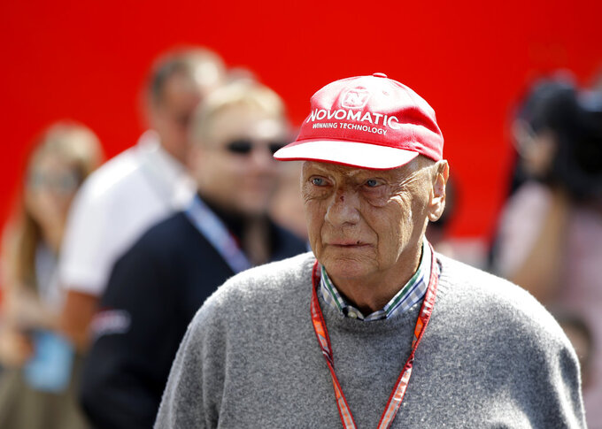 "FILE - In this July 7, 2018 file photo former Formula One World Champion Niki Lauda of Austria walks in the paddock before the third free practice at the Silverstone racetrack, Silverstone, England. Niki Lauda hopes to ""soon"" be back working with Mercedes as he continues his recovery from a lung transplant. The three-time Formula One champion was smiling and cheery as he posted a message on the Mercedes team's Twitter account on Saturday, Nov. 24. (AP Photo/Luca Bruno, file)"