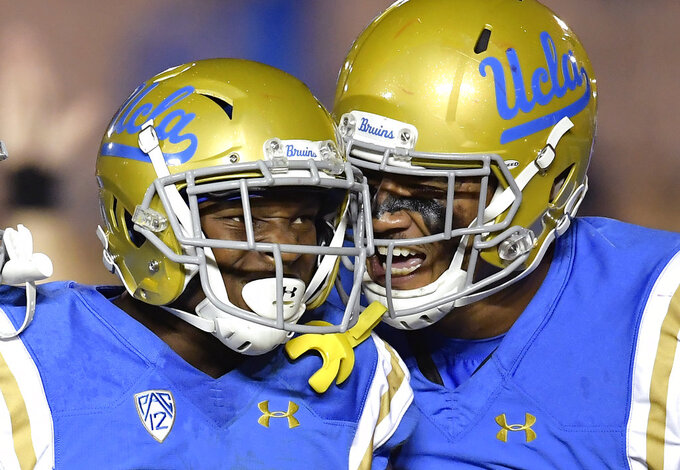 UCLA wide receiver Demetric Felton, left, celebrates his touchdown with tight end Devin Asiasi during the second half of an NCAA college football game against Arizona Saturday, Oct. 20, 2018, in Pasadena, Calif. UCLA won 31-30. (AP Photo/Mark J. Terrill)