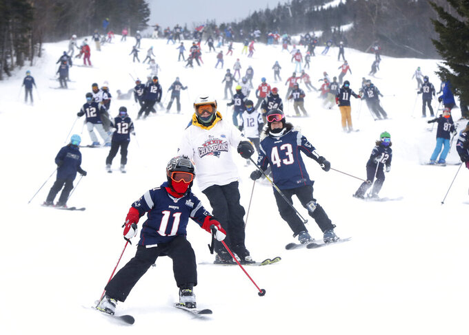 FILE - In this Feb. 3, 2019 file photo, New England Patriots fans head downhill at the Sugarloaf ski resort in Carrabassett Valley, Maine, prior to the NFL Super Bowl football game between the Patriots and the Los Angeles Rams. Thanks to an extended stretch of cold weather, the New England ski industry enjoyed one of best years in recent memory. (AP Photo/Robert F. Bukaty, File)