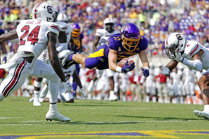 East Carolina's Tyler Snead (22) dives forward with the ball between South Carolina's Marcellas Dial (24) and Jaylin Dickerson (4) during the second half of an NCAA college football game in Greenville, N.C., Saturday, Sept. 11, 2021. (AP Photo/Karl B DeBlaker)