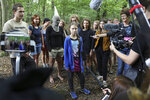Climate activist Greta Thunberg, center, stands together with environmentalist protesters and talk to media during a visit in the ancient Hambach Forest near the city of Kerpen in western Germany, Aug. 10, 2019. The teenage activist who is a leading figure in the Fridays for Future strikes against climate said that seeing the open-cast lignite pit in Hambach disturbed her deeply and that the time has come to stop talking and take action. Right are Luisa Neubauer a leading face of Germany's Friday for Future movement. (Oliver Berg/dpa via AP)