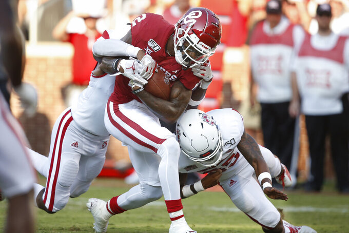 Oklahoma wide receiver CeeDee Lamb (2) is tackled by South Dakota defender Elijah Reed, left, and an unidentified defender at right, in the first quarter of an NCAA college football game Saturday, Sept. 7, 2019, in Norman, Okla. (AP Photo/Sue Ogrocki)