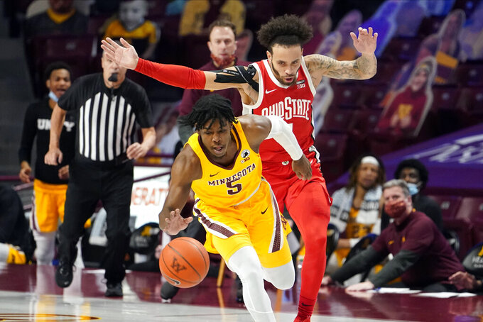 Minnesota's Marcus Carr (5) drives as Ohio State's Duane Washington Jr. (4) gives chase in the first half of an NCAA college basketball game Sunday, Jan. 3, 2021, in Minneapolis. (AP Photo/Jim Mone)