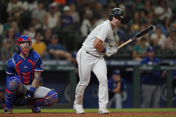 Seattle Mariners' Jarred Kelenic and Texas Rangers catcher Jonah Heim react after Kelenic walked with the bases loaded during the sixth inning of a baseball game Wednesday, Aug. 11, 2021, in Seattle. (AP Photo/Ted S. Warren)